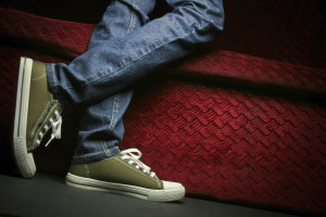 A teenager showing his/her shoes and jeans, posing in studio.